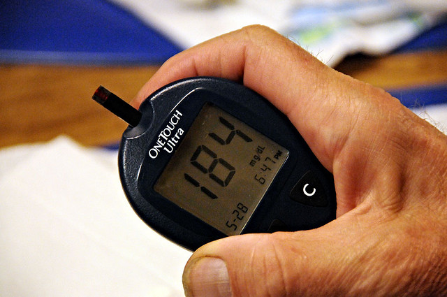 The meter displays blood sugar, 184 in this case